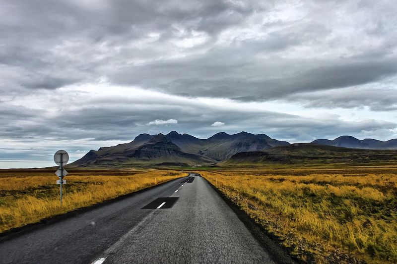 Road Passing Through Landscape Against Dramatic Sky