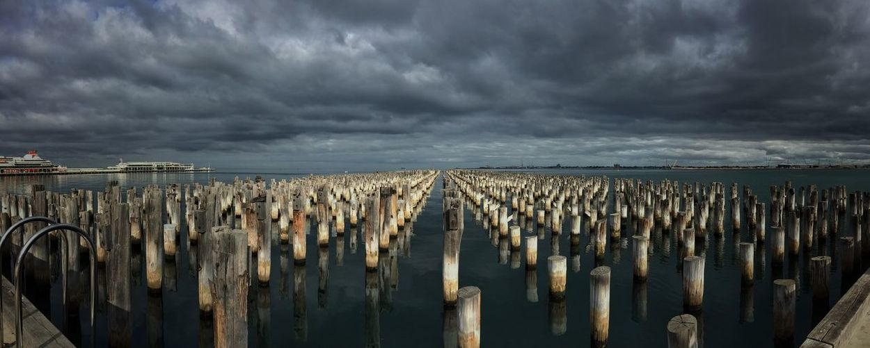 Wooden Post In Row At Princes Pier Against Cloudy Sky