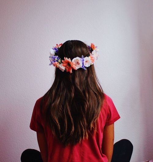 Rear view of girl standing against pink flowers