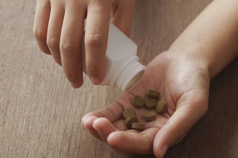 Cropped hands of person holding medicine bottle on wooden table