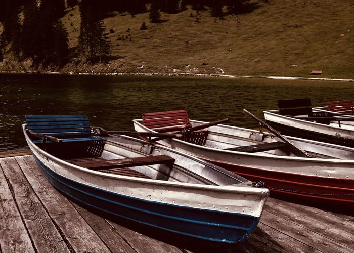 Boats moored on pier by lake