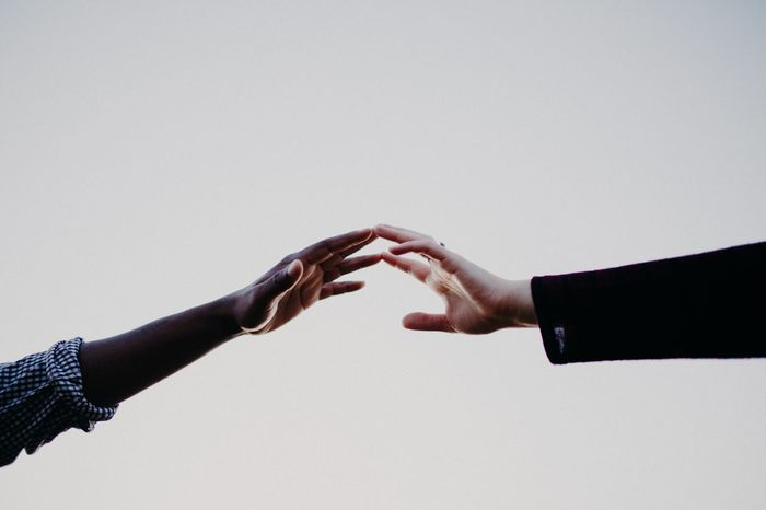 Close-up of couple reaching over white background
