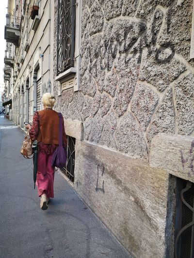 Rear view of woman walking on street against building