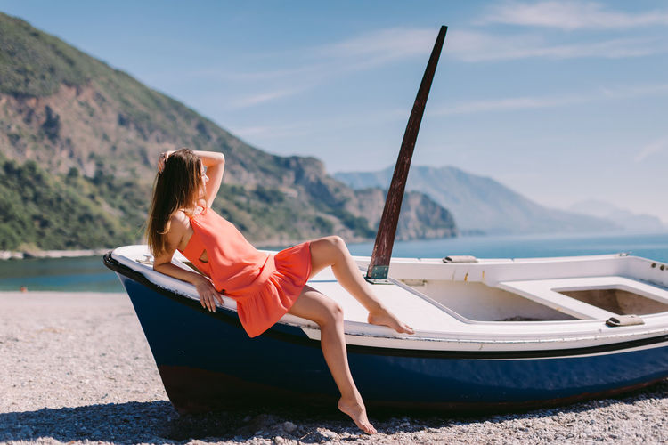Woman sitting on boat at beach against sky