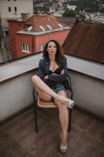 Portrait of woman sitting on chair in city
