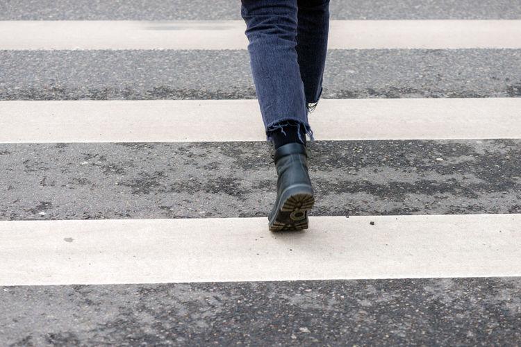 Low Section Of Woman Walking On Zebra Crossing