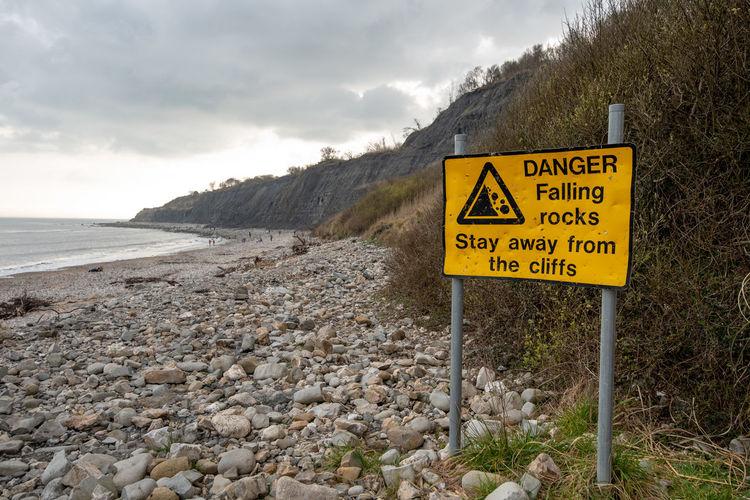 A bright yellow Danger sign warning of Falling Rocks from the cliffs along the Lyme Regis fossil beach, Dorset, UK. Danger Dorset Cliff Face Cliffs Erosion Falling Rocks Fossil Hunting Fossils Jurassic Coast Lyme Regis Rocks Sign Stone Beach Stones Communication Text Cloud - Sky Warning Sign Sky Nature Western Script Water Yellow No People Guidance Day Mountain Scenics - Nature Tranquility Road Safety Land