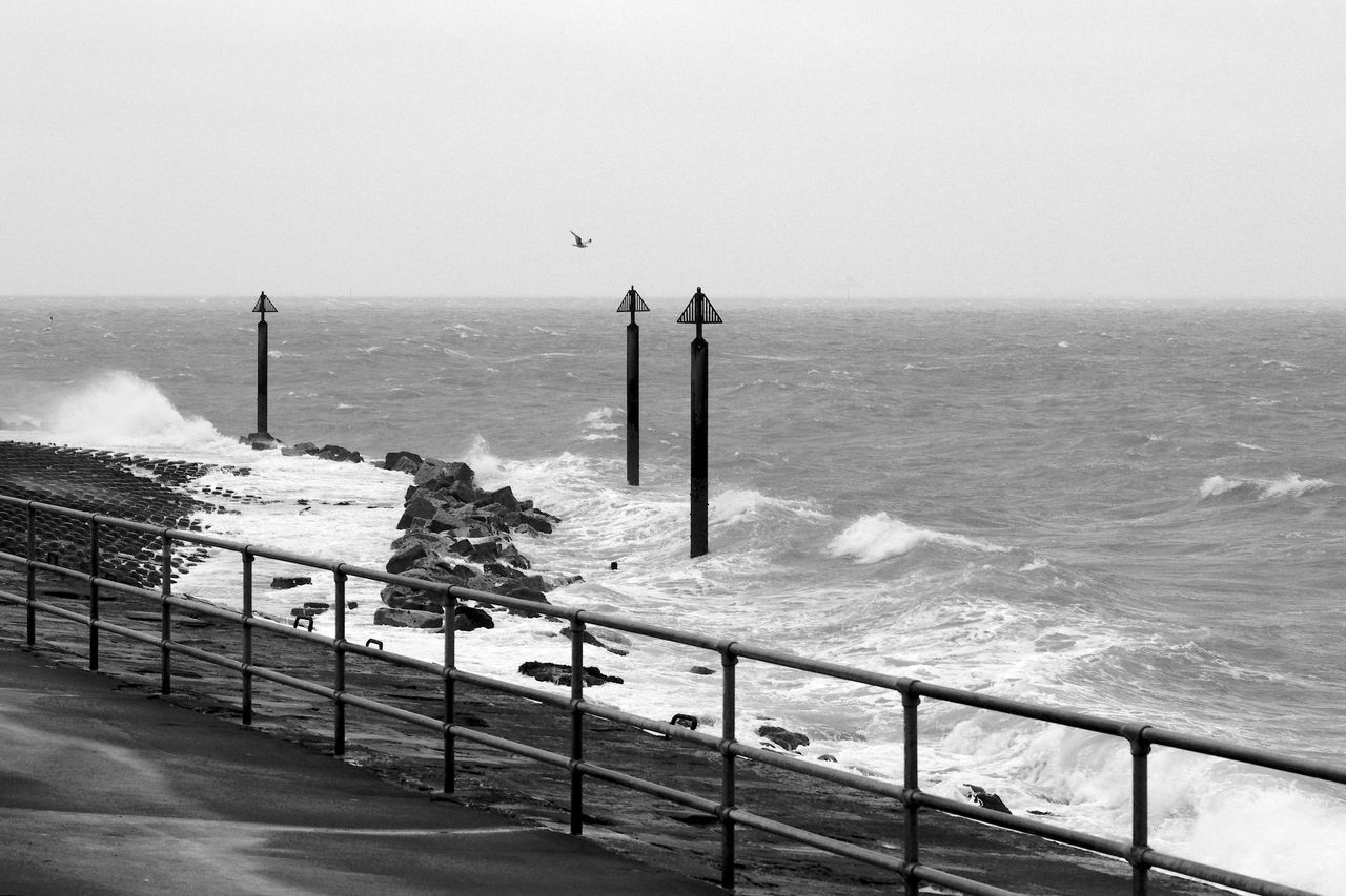 sea, water, horizon over water, horizon, sky, wave, railing, nature, scenics - nature, land, beauty in nature, motion, beach, day, no people, clear sky, sport, outdoors, architecture, breaking, hitting, power in nature