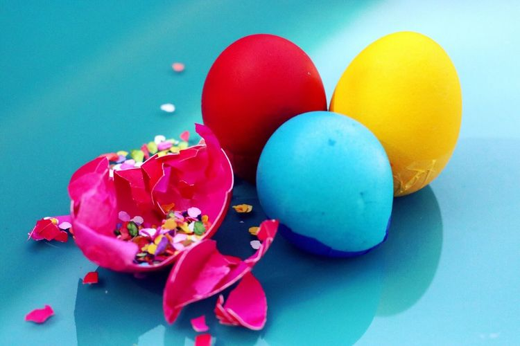 Close-up of broken easter egg on turquoise background