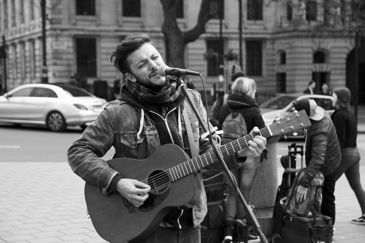 music, real people, musical instrument, outdoors, arts culture and entertainment, musician, street, playing, guitar, performance, building exterior, standing, men, city, skill, built structure, architecture, day, plucking an instrument, adult, people