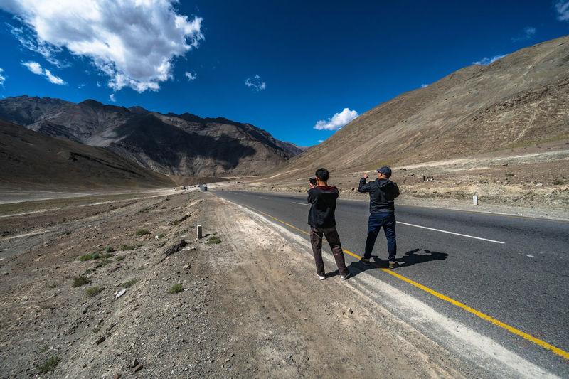 People on road against mountain range