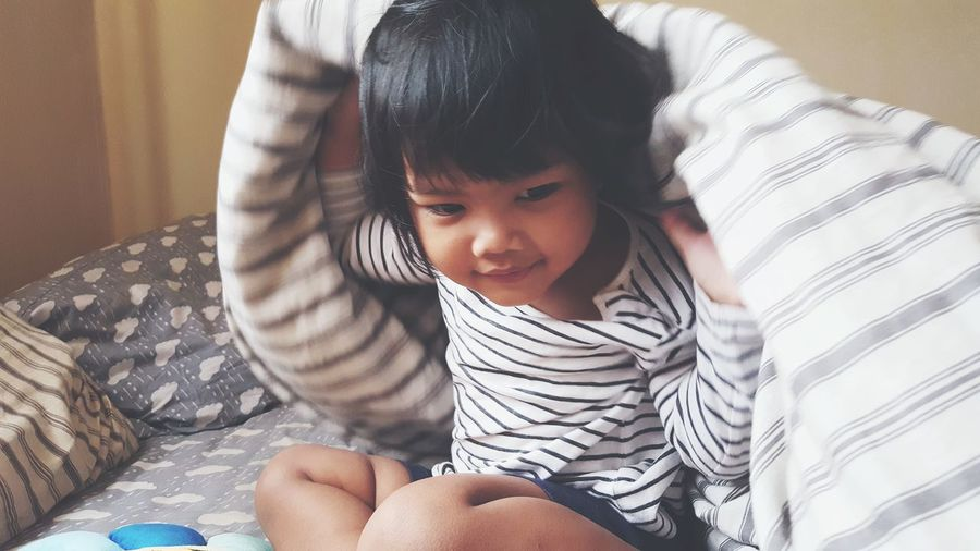 Close-up of cute girl sitting on bed at home
