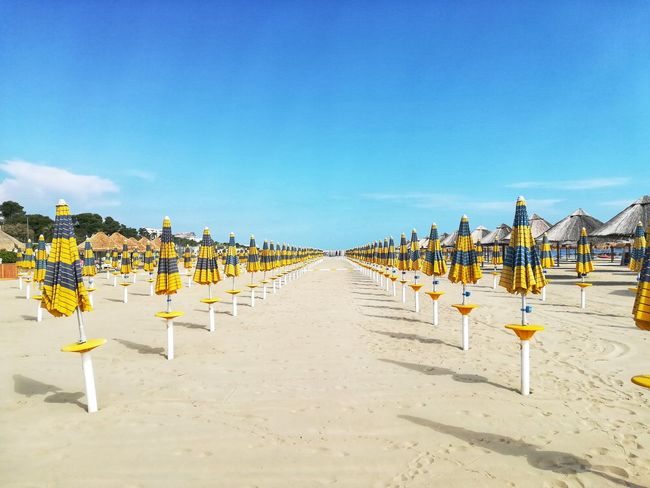 Emptybeach Nobody Shadows Travel Vacation Bathhouse Summer Clear Sky Row In A Row Personal Perspective Beach Umbrellas Lined Up Beach Umbrellas Closed Beach Umbrellas Beach Sand Blue Sea Sunny Sky Repetition