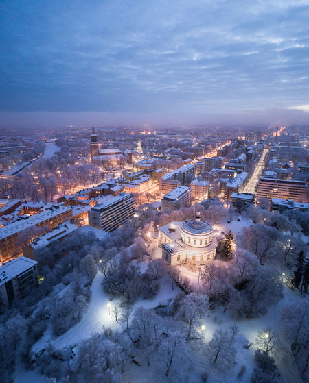 Aerial view of illuminated buildings in city during winter