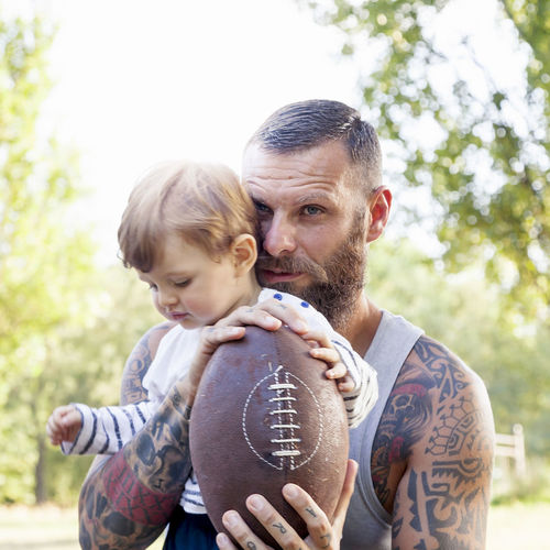 portrait of tattooed father and his son in the park with rugby ball Men Family Togetherness Child Happy Embrace Bearded Man Rugby Ball Tattoo Casual Clothing Day Love Bonding Positive Emotion Outdoors Park People Adorable Caucasian Kid Plant Meadow Parent Males  Father Family With One Child Childhood Real People Emotion Son Innocence