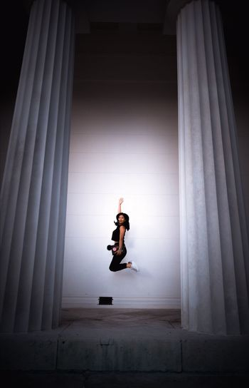 Full length of woman jumping against white wall