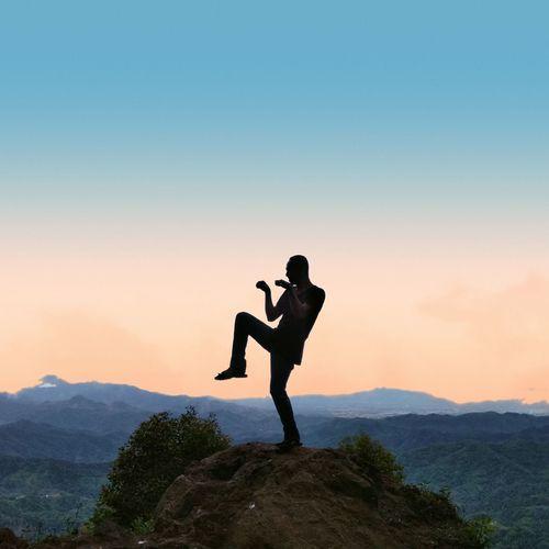 Full length of man standing on rock against sky during sunset.