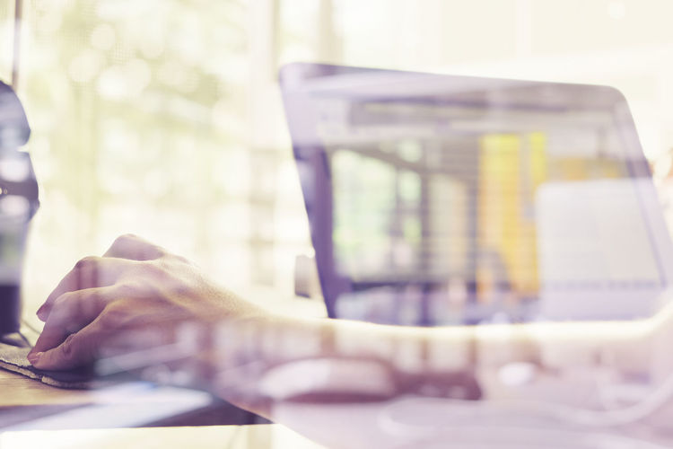 Close-Up Of Woman Using Laptop At Desk