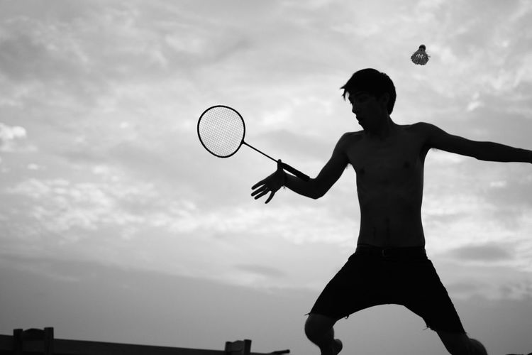 Arms Raised Badminton Balance Birdie Cloud Cloudy Day Enjoyment Freedom Fun Funny Jumping Leisure Activity Lifestyles Low Angle View Mid-air Motion Outdoors Racket Sillouette Skill  Sky Sport Stunt Vacation