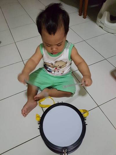 Playing drum. Drum Child Childhood Sitting Full Length Playing Fun Looking Down Baby Toddler