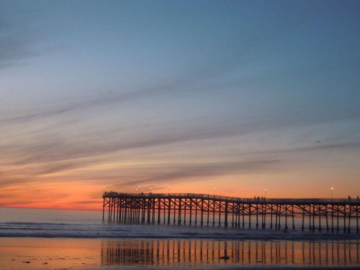 Silhouette Pier On Shore Against Sunset Sky