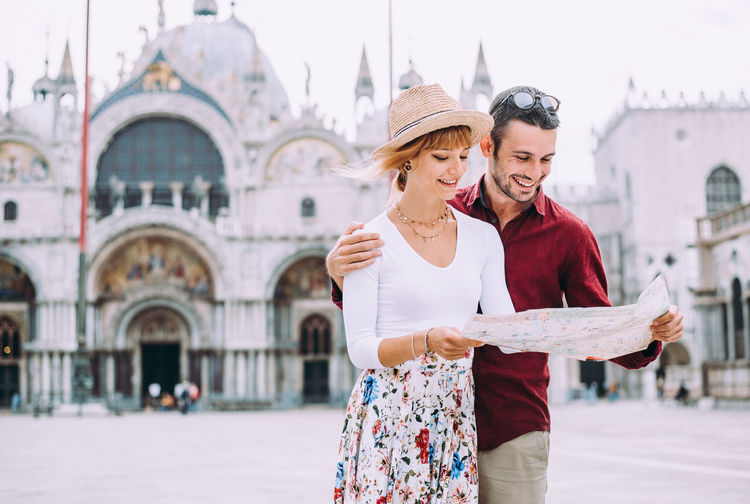 Couple holding map standing against building outdoors
