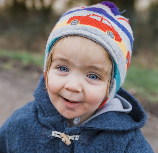 Portrait of toddler girl with blue eyes – Kempen, Germany Baby Blond Blue Eyes Carefree Casual Caucasian Cheerful Child Childhood Close-up Coat Communication Confidence  Contemplation Cute Duffle Emotion Expression Face Field Footpath Germany Girl Grass Gravel Grimacing Happy Hat HEAD Head And Shoulders Headshot Jacket Knit Looking Nature One Outdoors Pensive People Portrait Road Serious Talking Tired Toddler  Warm Clothing Watching Winter Wool Yawning One Person Real People Clothing Focus On Foreground Front View Innocence Day Boys Knit Hat Hood - Clothing