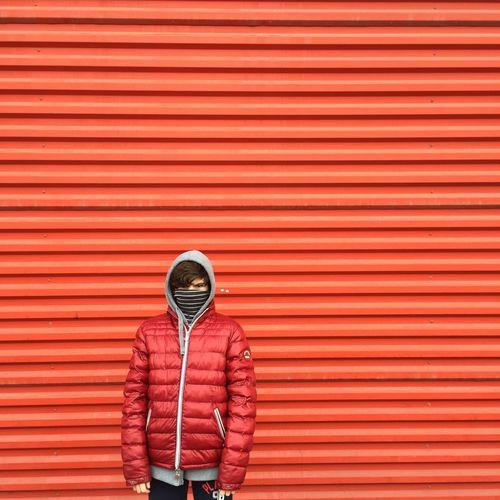 Full length of man standing on red umbrella