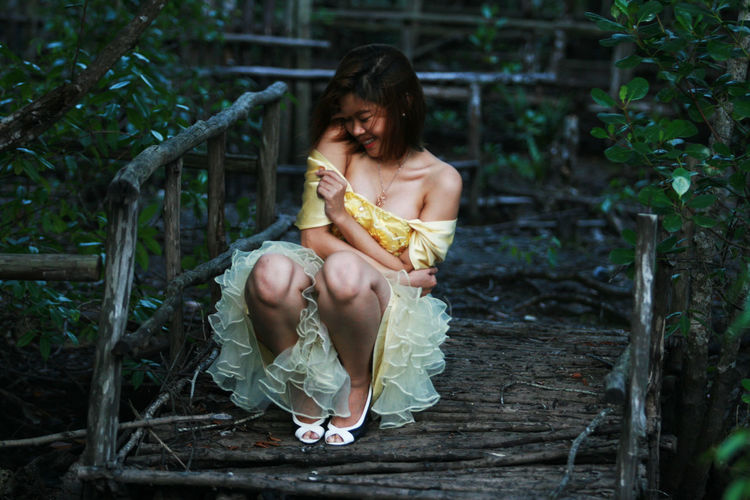 Laughing young woman posing in dress outdoors
