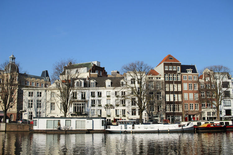 Typical Amsterdam houses at a canal Amsterdam Architecture City City Life Clear Sky Netherlands Tourist Attraction  Amsterdamcity Architecture Blue Sky Boats Canal Canals And Waterways City Day Daylight No People Tourist Destination Urban Water Waterfront