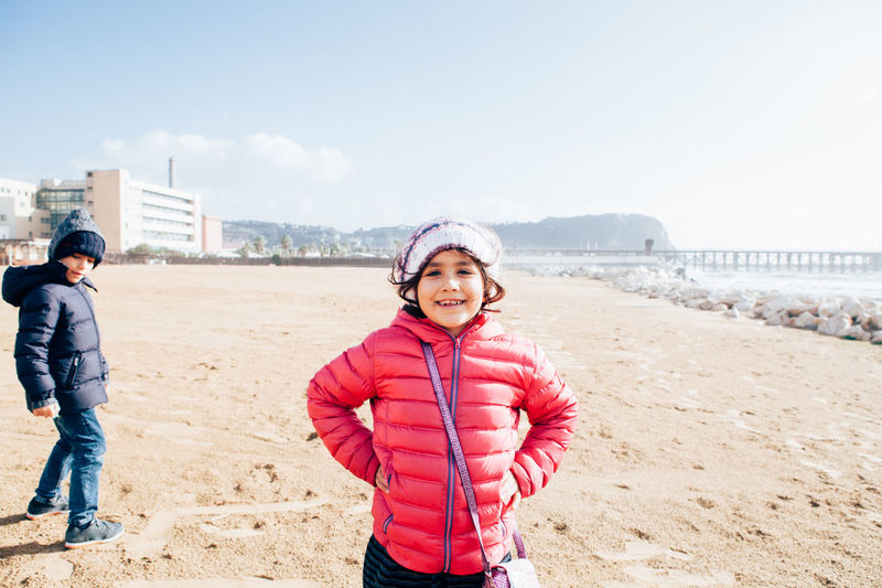 Portrait of smiling girl standing at beach against sky