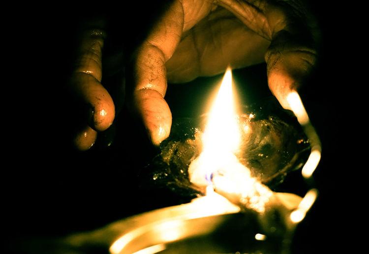Close-up of person hands lighting diya
