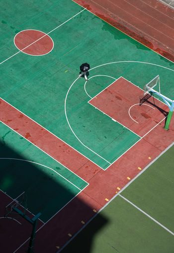 High angle view of person holding umbrella walking on basketball court