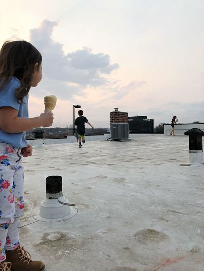 Side view of girl with ice cream cone standing on building terrace against sky