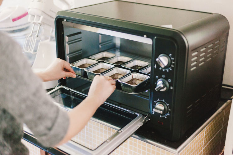 Cropped Image Of Woman Cooking Food In Oven