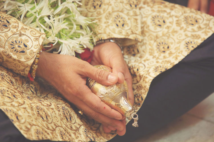 Midsection of groom with jewelry sitting on floor during wedding ceremony