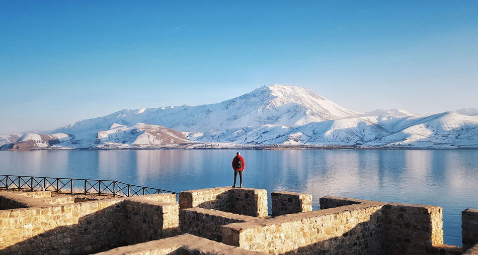 Rear view of man standing on stone wall by lake during winter