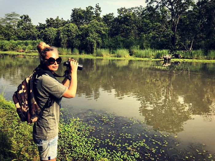 Woman Holding Binocular While Standing By Lake At Forest On Sunny Day