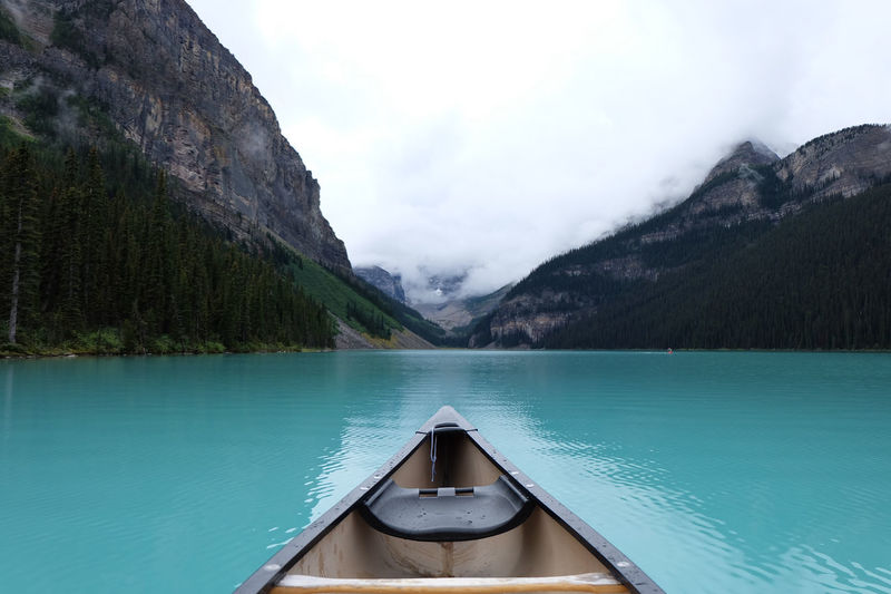 Scenic view of lake and mountains seen through boat against sky