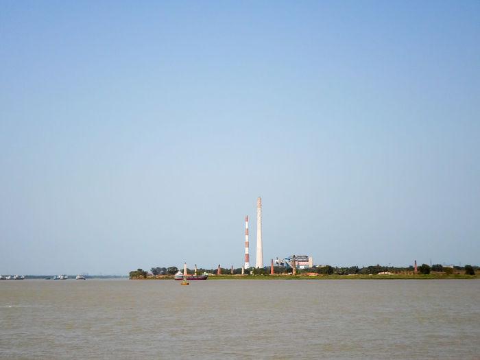 Lighthouse in sea against clear sky