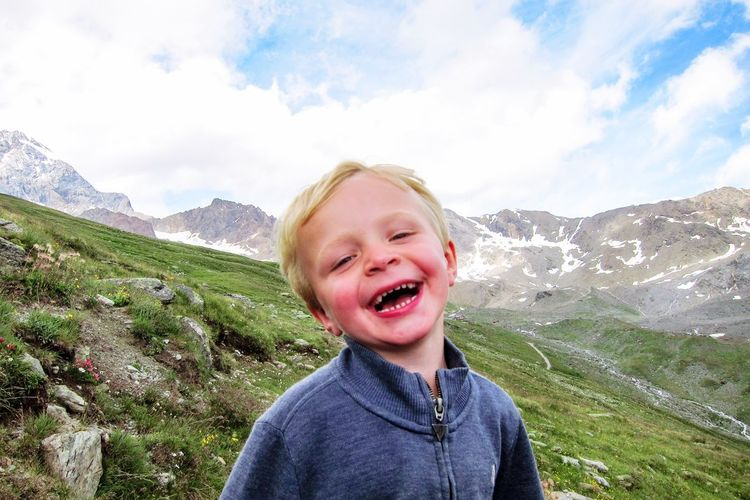 Portrait of smiling boy standing on landscape against sky
