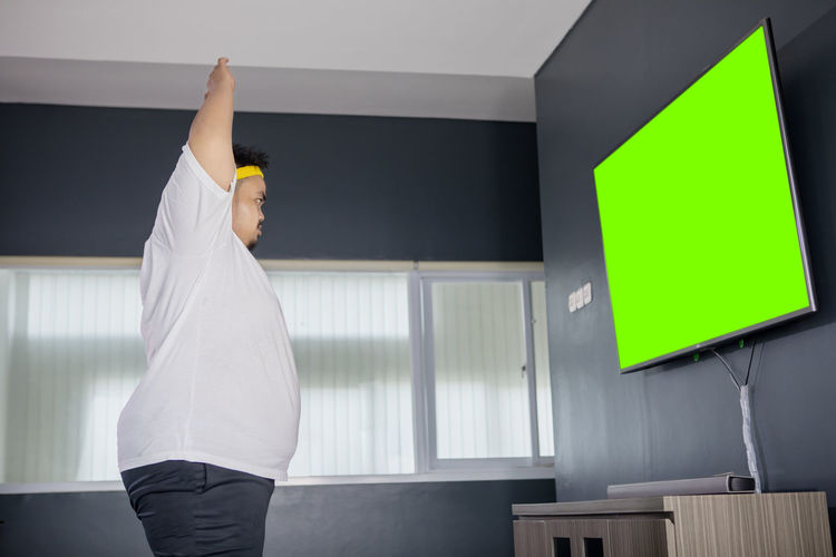 Side view of man with arms raised looking at lcd screen at home