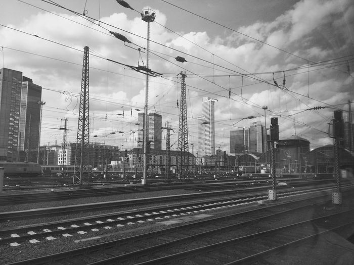 Railroad Tracks And Electricity Pylons Against Cloudy Sky