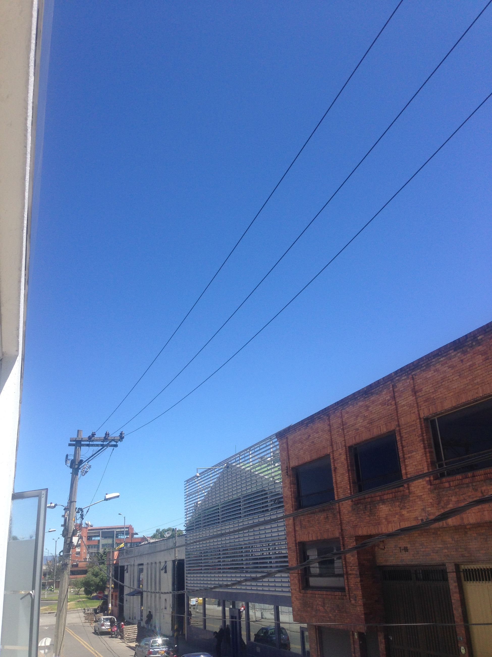 low angle view, power line, clear sky, building exterior, architecture, built structure, cable, blue, bird, connection, electricity, electricity pylon, animal themes, wildlife, power supply, animals in the wild, outdoors, sky, day, power cable