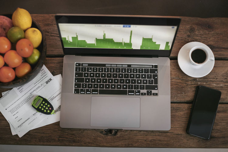 High angle view of apples and laptop on table