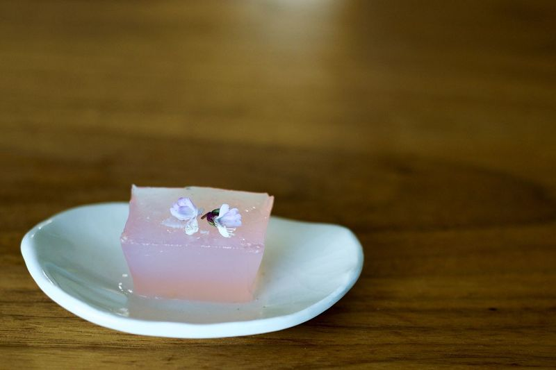 Close-up of gelatin dessert garnished with flower in plate on table