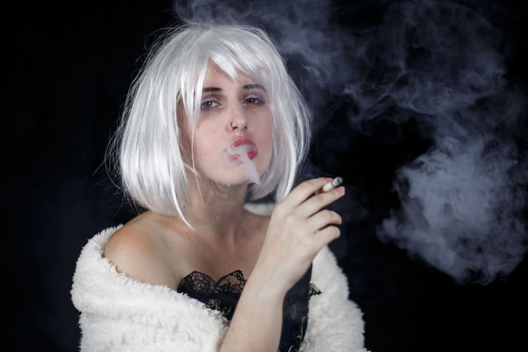 Attractive young woman in costume smoking cigar and looking at camera while standing on black background Beautiful Elegant Lady Posh Retro Vogue Woman Young Addiction Attractive Character Cigar Costume Delight  Female Fringe Girl Glamour Hairstyle Luxury Model Studio Shot Style Vintage Wig