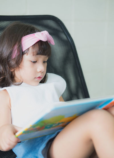 Close-up of girl looking away while sitting at home