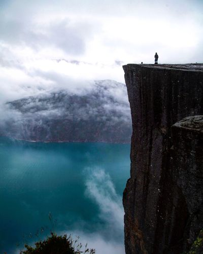 Distant view of man standing on huge cliff overlooking river