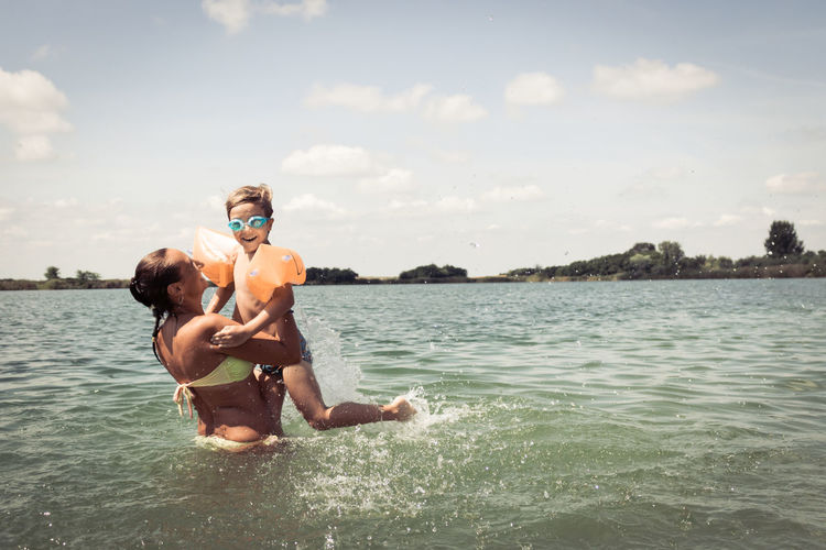 Woman playing with son in sea against sky